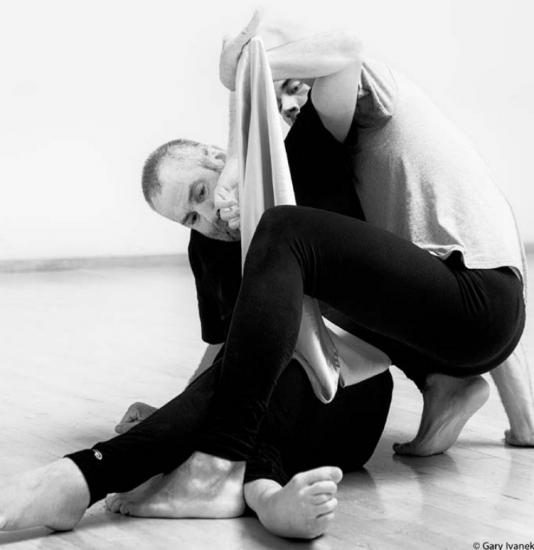 Neil Marcus engaging in a contact improvisation performance. The two dancers look intertwined with each other. Courtesy of Neil Marcus and Gary Ivanek.