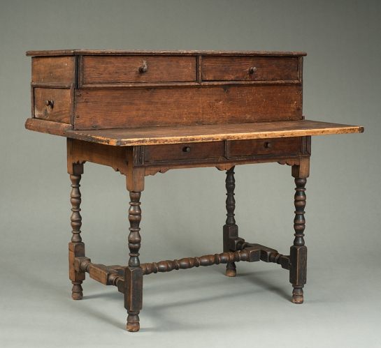 Table-Desk. Probably Springfield, Massachusetts ca. 1690, hard maple, white pine, yellow pine, iron Museum Purchase with partial funds given in memory of Lawrence K. Wagenseil. Photograph courtesy of Historic Deerfield.  The upper portion of this piece was made with writing in mind.  By designing the middle drawers to open sideways, the unknown craftsman made sure that anyone writing at the table-desk would not have to move his or her papers in order to access the drawers.  Similarly, the upper drawers are high enough above the writing surface to prevent paper-shuffling.  Additionally, the two long, side drawers span the width of the table-desk, offering ample room for storing books and materials.