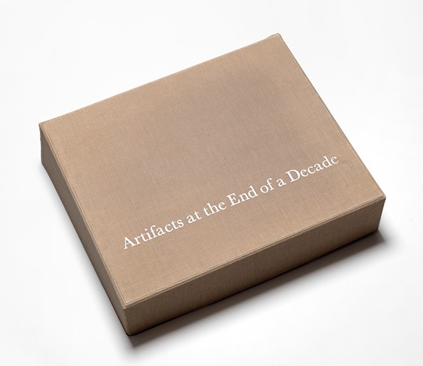 "An image of an to closed archival box containing the artists Watson and Venezia-Huebner's portfolio with the title ""Artifacts at the end of a Decade"" on the cover of the box."