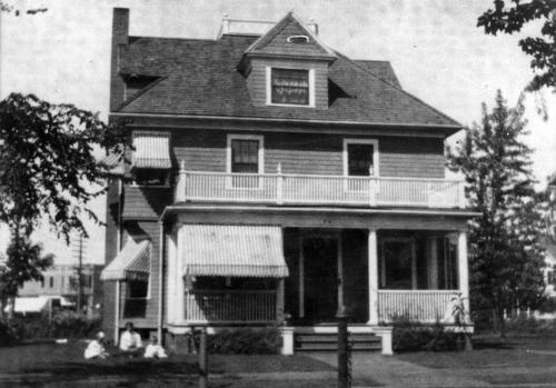 Black and white photograph of a large clapboard house with front porch and awning. Three people in white sit in the lefthand corner of the image.